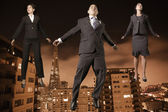 Businesspeople floating above the city — Stock Photo