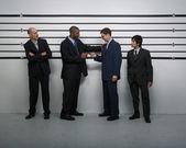 Multi-ethnic businessmen in police line up — Stock Photo