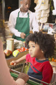 Young African American boy in shopping cart at supermarket checkout — Stock Photo