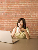 Young woman using a laptop and having a cup of coffee — Stock Photo