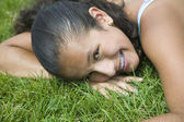 Hispanic girl laying in grass — Stock Photo