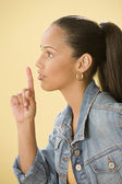 Studio shot of a female Dominican teenager putting index finger to lips — Stock Photo