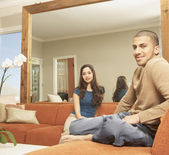 Young Hispanic couple sitting on the sofa — Stock Photo