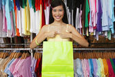 Portrait of woman in clothing store holding bag — Stock Photo