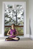 Kobieta siedzi na podłodze medytując — Zdjęcie stockowe