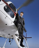 Asian businessman on helicopter — Stock Photo