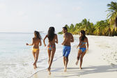 South American friends running at beach — Stock Photo