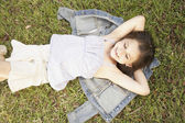 High angle view of Hispanic girl lying in grass — Stock Photo