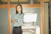 Businesswoman leaning on copy machine — Stock Photo