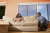 Man moving couch with woman sitting on it — Stock Photo