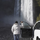 Man in winter jacket leaning on truck and looking at waterfall — Stock Photo