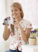 Hispanic woman holding video camera — Stock Photo