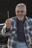Senior man glimlachend en houden schroevendraaier — Stockfoto