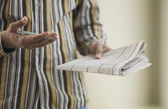 Close up of African man with pen and newspaper — Stock Photo
