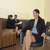 Businesswoman sitting with co-workers in background — Stock Photo