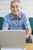 Portrait of elderly man with laptop — Stock Photo
