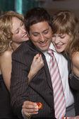 Man gambling as women fawn over him — Stock Photo