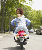 African American couple riding motor scooter — Stock Photo
