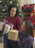 Couple with gifts in front of Christmas tree — Stock Photo