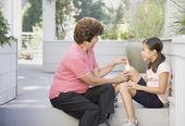 Asian grandmother bandaging granddaughter's knee — Stock Photo