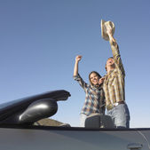 Couple in convertible celebrating — Stock Photo