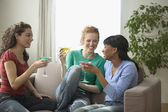 Three women talking and drinking mixed drinks — Stock Photo