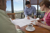 Man showing house plans to couple — Stock Photo