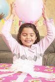 Young Hispanic girl with large gift and balloon — Stock Photo