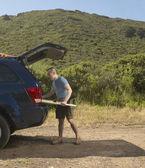 Tavola da surf imballaggio uomo in suv — Foto Stock