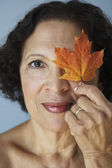 Senior African woman holding autumn leaf over eye — Stock Photo
