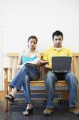Kvinna läser och man använder laptop — Stockfoto