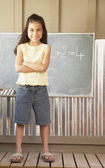 Hispanic girl standing in front of blackboard — Stock Photo