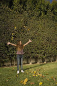 Hispanic girl playing in leaves — Stock Photo