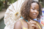 Woman holding a parasol outdoors — ストック写真