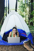 Woman using laptop in tent — Stock Photo
