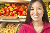 Asian woman in produce section of grocery store — Stock Photo