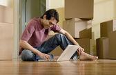 Hispanic man typing on laptop in new house — Stock Photo