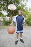 Young boy dribbling basketball — Stock Photo