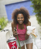 African American woman holding hose and soapy cloth — Stock Photo