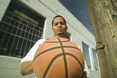 Young man bouncing a basketball — Stock Photo