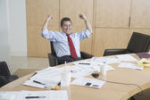 Hispanic businessman cheering at conference table — Stock Photo