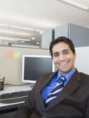 Businessman sitting in cubicle smiling — Stok fotoğraf