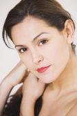 Close up studio shot of Hispanic woman touching hair — Stock Photo