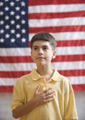 Boy in front of American flag with hand over heart — Stok fotoğraf