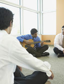 Businessman playing guitar with coworkers — Stock Photo