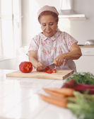Senior Hispanic woman chopping vegetables — Stock Photo