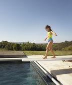 Young girl walking on diving board — Stock Photo