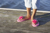 Young woman wearing pink daisy flip-flops — Stock Photo