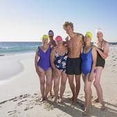 水着でビーチで若い男性と年配の女性のグループ — ストック写真