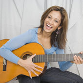 Indian woman playing acoustic guitar — Stock Photo